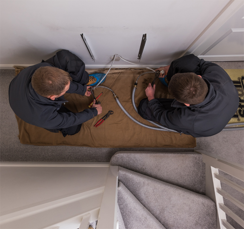 Two members of staff installing radiator
